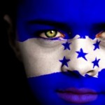 Portrait of a boy with the flag of Honduras painted on his face.